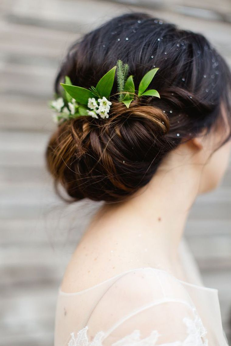 low tied bun with greenery as hair piece. brides with buns via