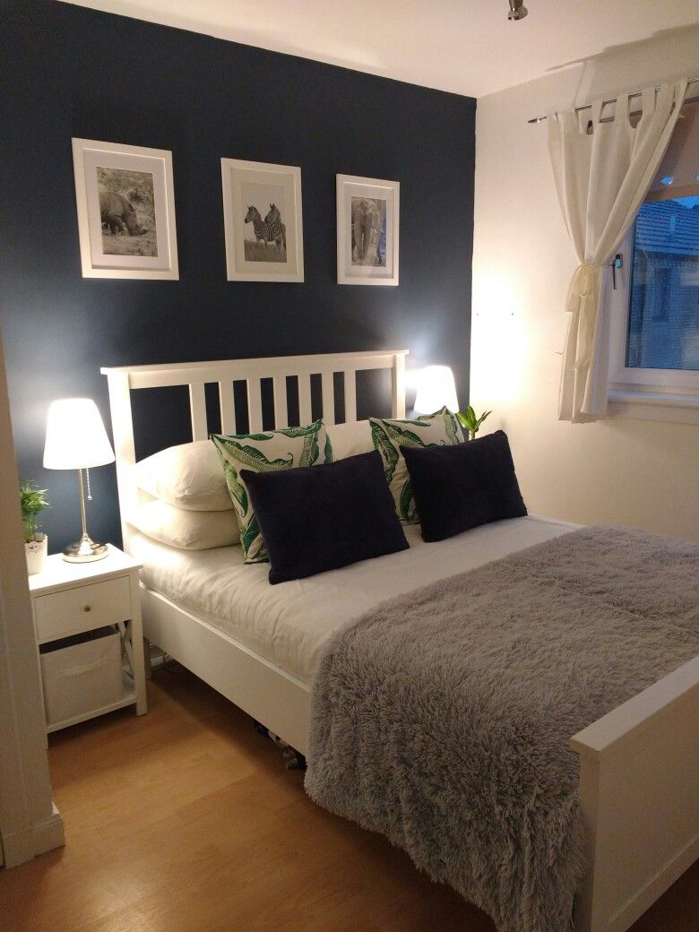 Dark blue and white small double bedroom with accents of ...