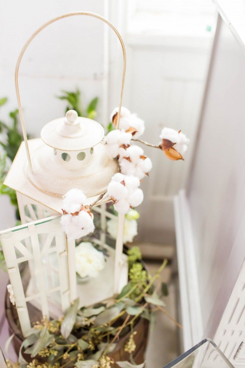 Wedding decor. lantern with cotton blossoms and seeded eucalyptus on ...