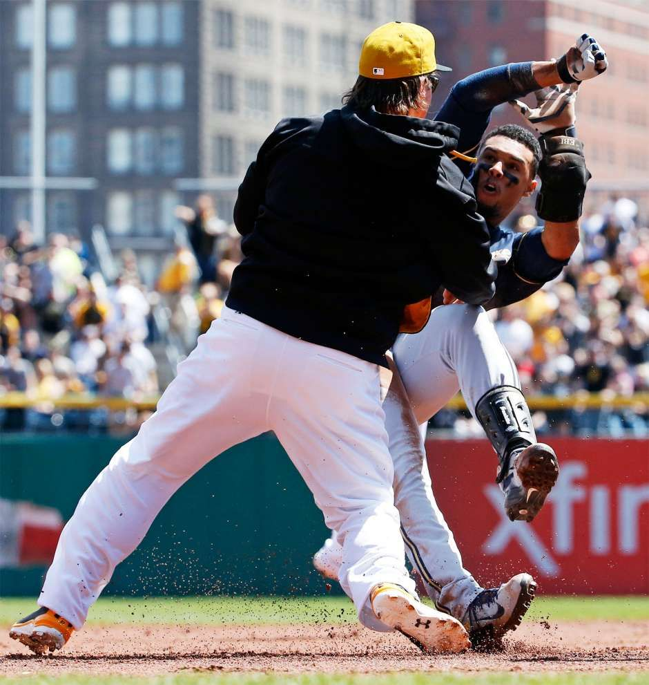The Pittsburgh Pirates' Travis Snider, left, takes down