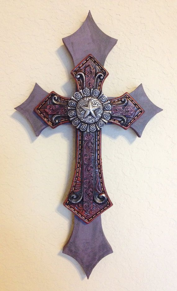 """Small wooden, double layer, wall cross. Painted with black and purple acrylic paint. The piece is topped with a faux tooled red leather cross with contrast stitching and topped with an ornate silver Texas star emblem. Dimensions are approximately 6"""" x 11"""". Each cross is handmade with love and truly one of a kind."""