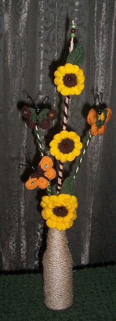 Arreglo de girasoles y mariposas hechas en lana con base de botella de cerveza forrada de soga.