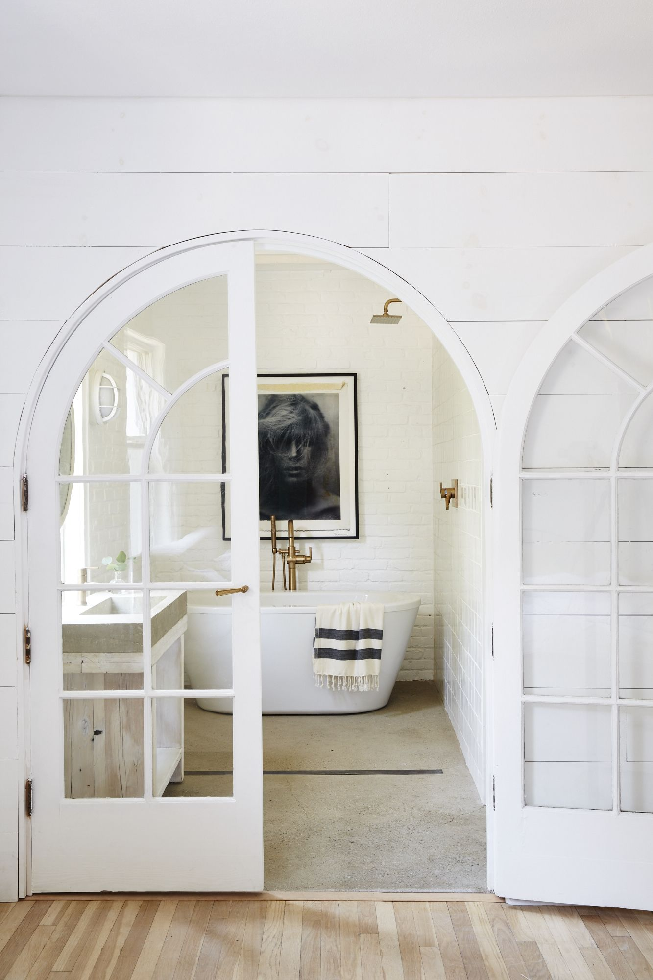 Arched french doors to bathroom with stand alone bathtub with black