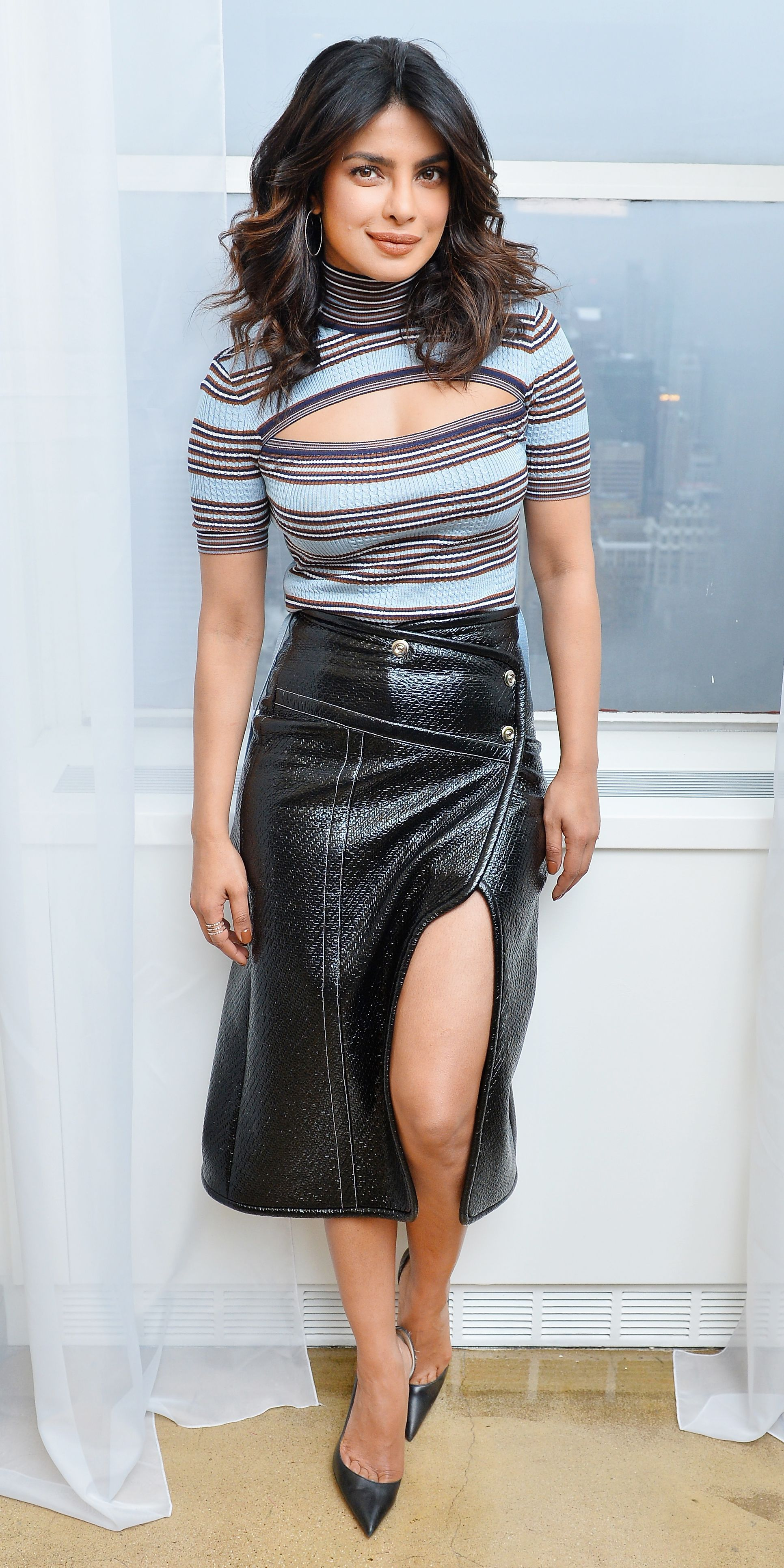 6d482885c54 Priyanka Chopra proved that turtlenecks don t have to be boring with a  stripe design featuring a strategically placed cutout. A patent leather  skirt with a ...