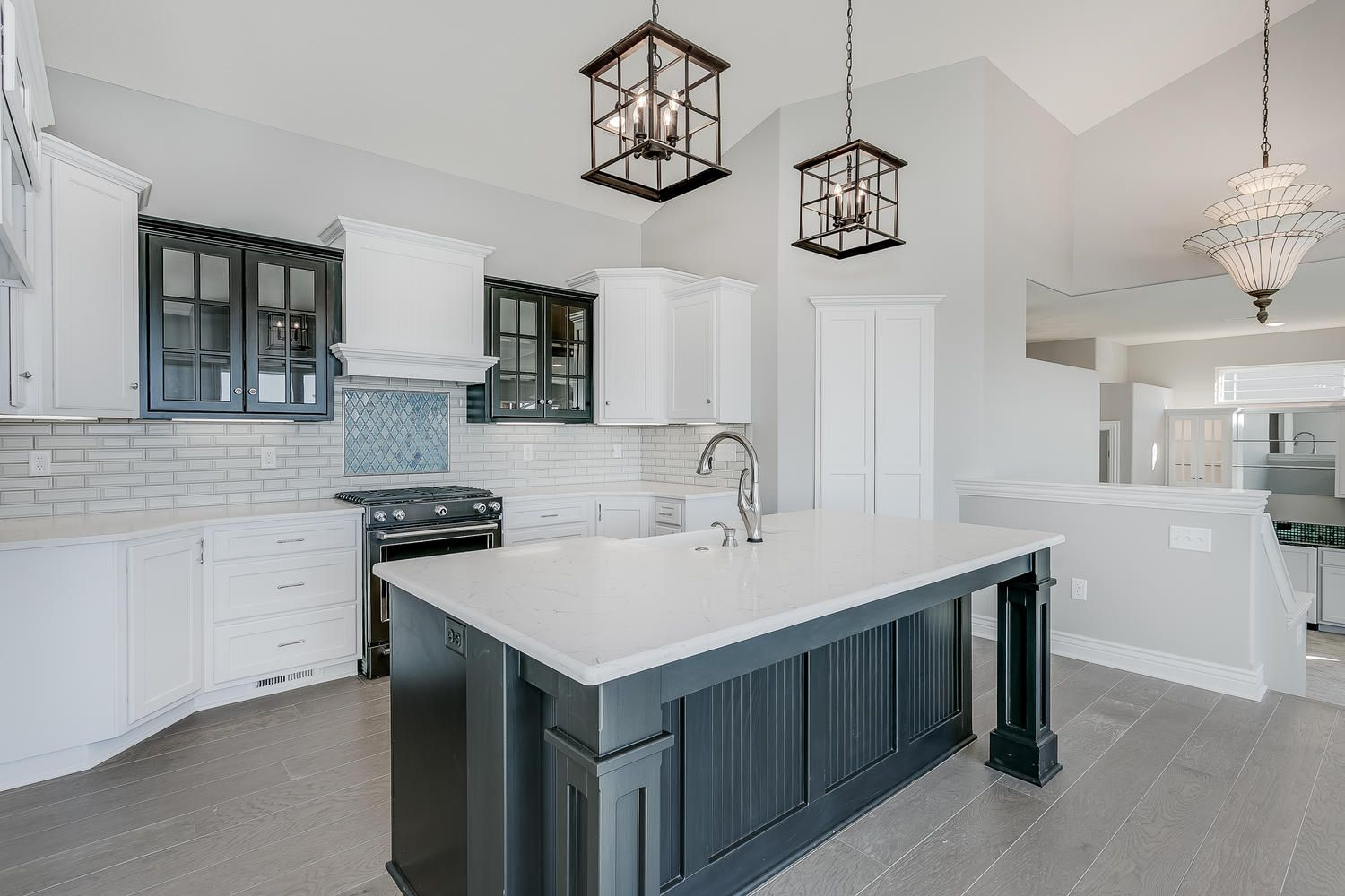White cabinets and black wood finished kitchen island with ...