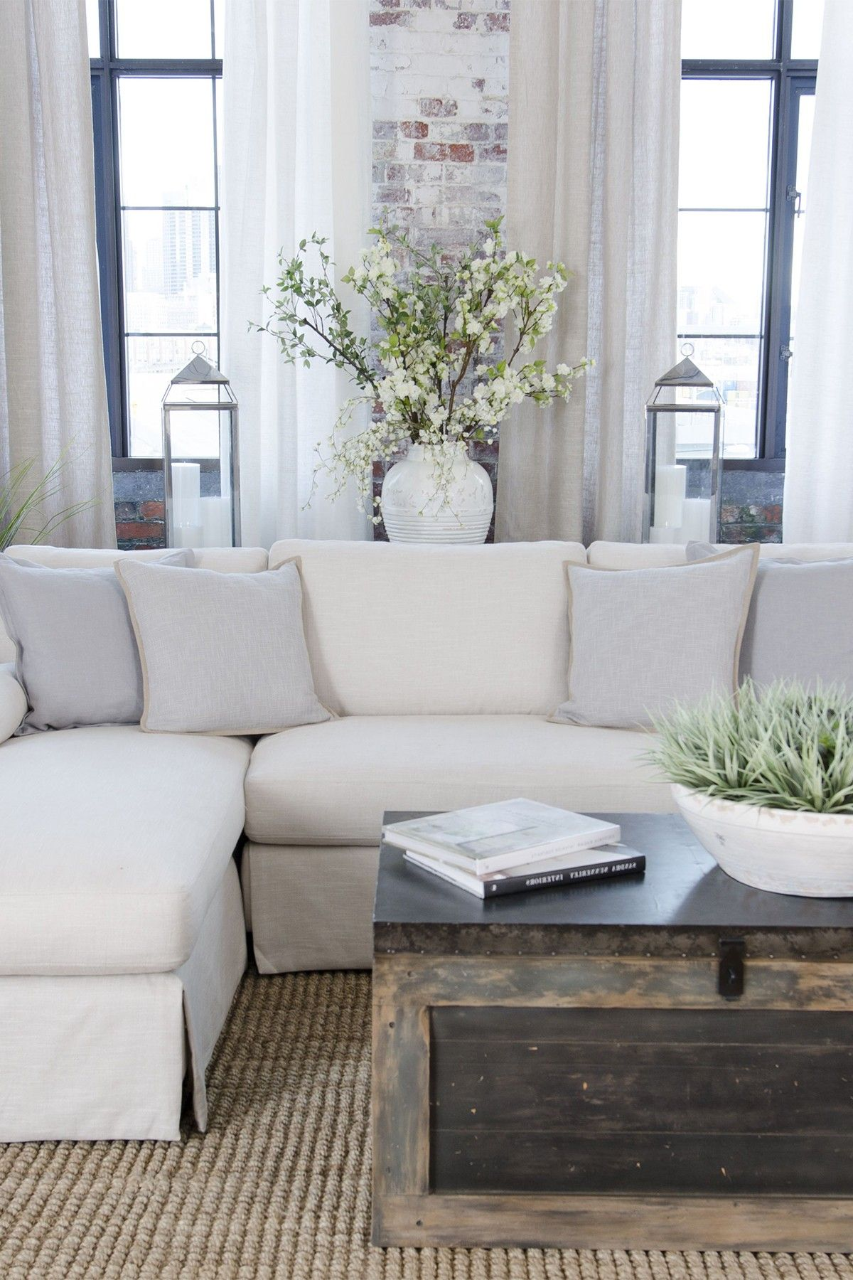 white sectional with pale blue throw pillows via Pamela Prussel ...