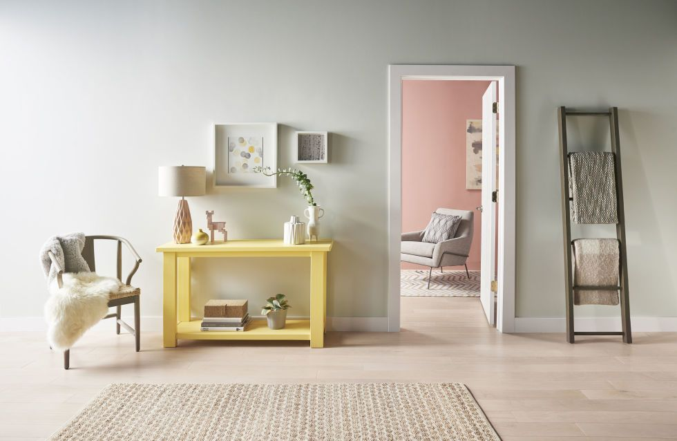 Bright Accent Pieces Like The Soft Yellow Console Energize This Room S Muted Gray Walls