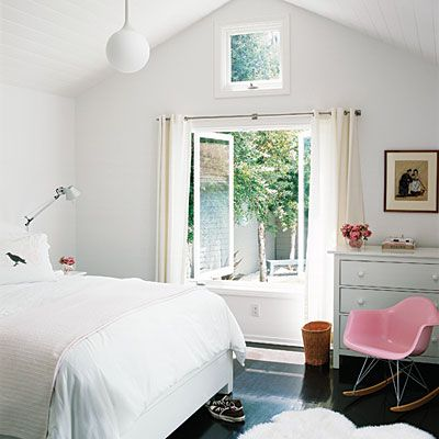 Keeping walls and linens white makes a small space look bigger and airier. Adding a small pop of color, like this pink chair, keeps the space lively.
