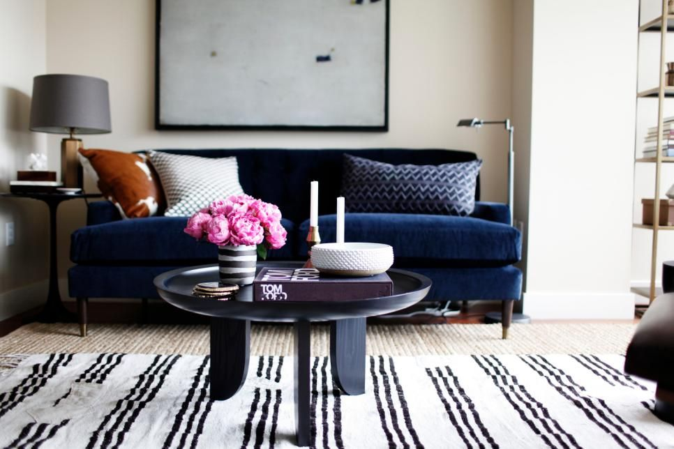 A thin blackandwhite striped rug layered over a jute rug works