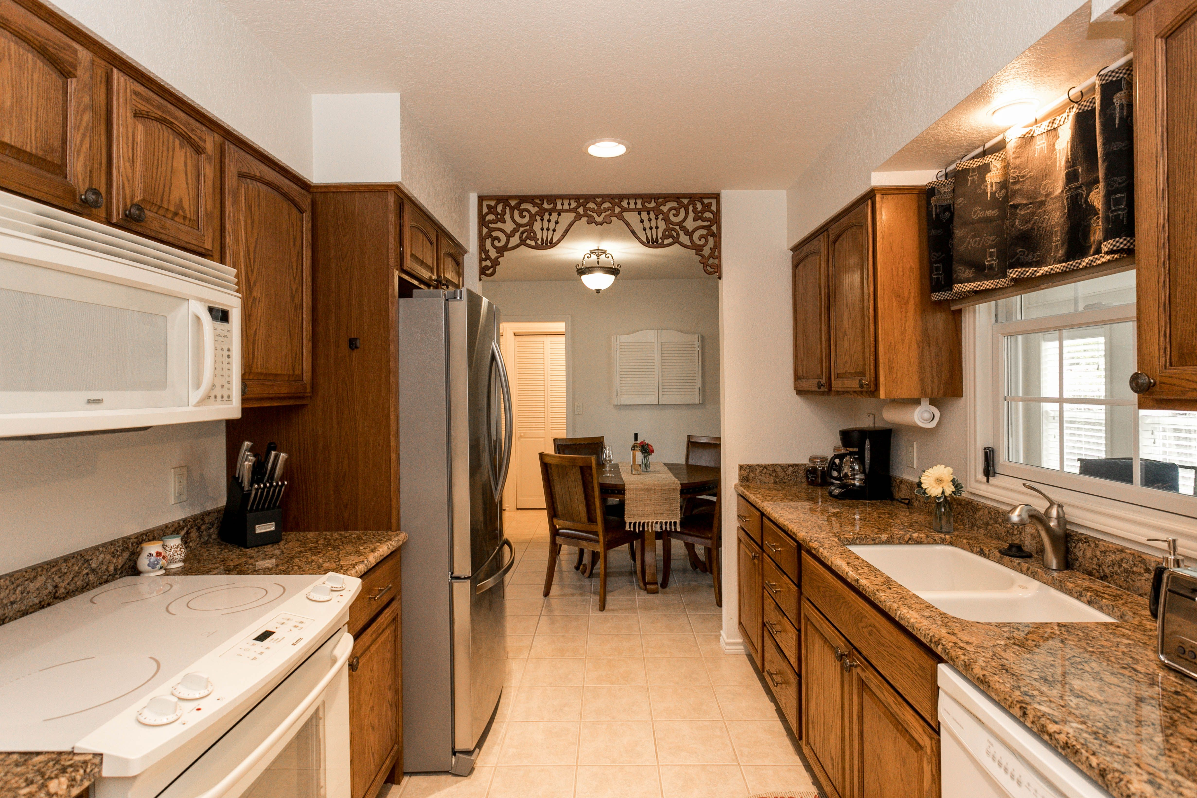A spacious galley-style kitchen is accented by granite ...