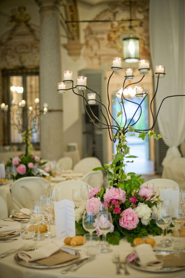 Wedding table centerpiece with flowers & candles.