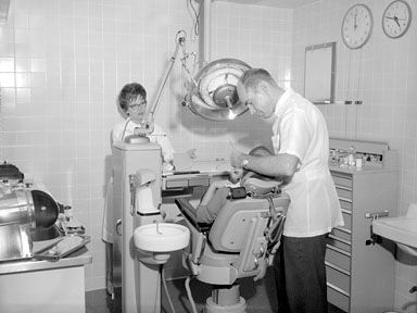 Dentist Working Patient October 18 1962 Black White 1960s Archive Chair Clock Dental Equipment Examination Health
