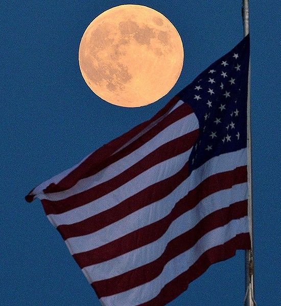 Full moon rises over the American flag during the baseball