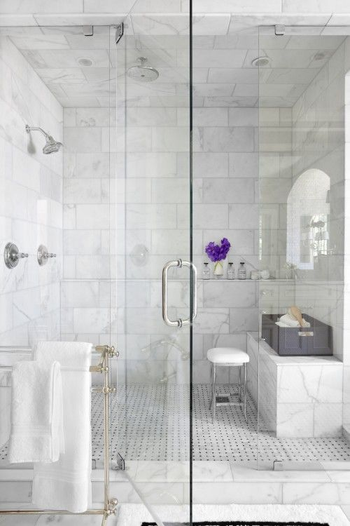 Seamless glass shower enclosure. Marble shower.  bench along portion of wall.
