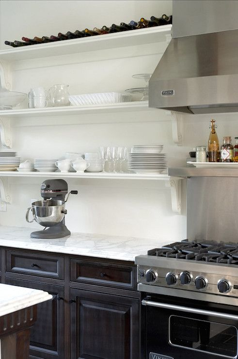 Gorgeous kitchen features espresso cabinetry paired with a white marble countertop below stacked shelves with corbels alongside a Viking Range with stainless steel warming shelf attached to stainless steel cooktop backsplash below a Viking Hood.