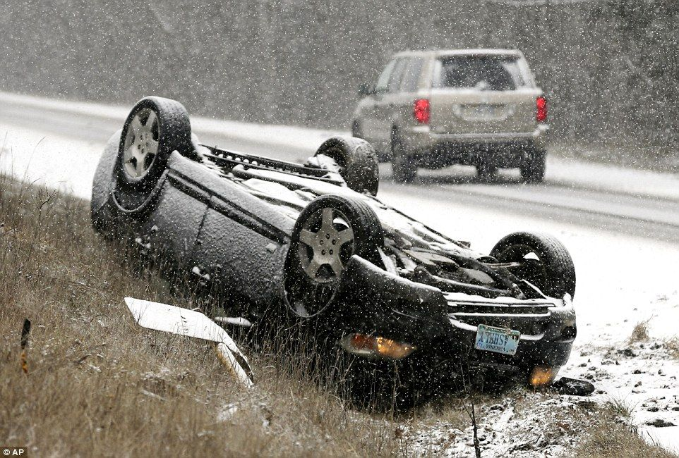 An overturned vehicle rests on the shoulder of a snow-covered road near Gainesboro, Virgin...