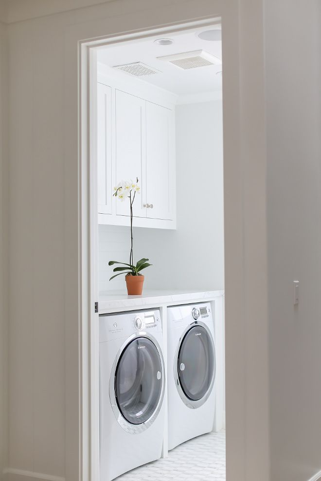 White Laundry Room Features White Cabinets Over An Enclosed Electrolux  Washer And Dryer Alongside A White Mosaic Marble Floor.