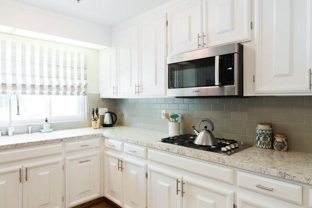 An Update Kitchen With White Cabinets And Taupe Ceramic Backsplash Tiles White Kitchen Cabinets Brick Backsplash Kitchen Updated Kitchen