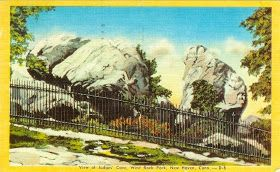 West Rock Trails: West Rock Historic Postcards, showing Judges Cave with a fence around it, the way it was when the book Ginger Pye takes place.