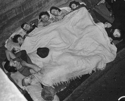 Children and an adult share a blanket and sleep in their bomb shelter in southwest London, 1940