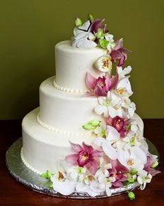 Three Tier White Wedding Cake Decorated With Fresh Pink And Cascading Orchid Flowers From