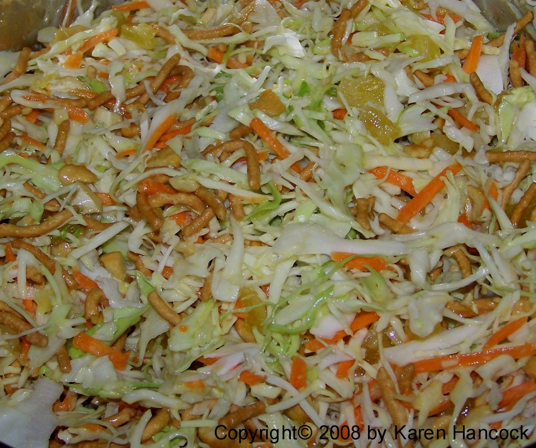 ASIAN GINGER COLESLAW: 1 1/2 lb coleslaw mix, 4 green onions including tops sliced, 1 cp soy nuts, or coarsely chpd cashews, 1 cp dried pineapple wedges, coarsely chpd, 2 cps chow mien noodles. Dressing: 2 one in. pieces fresh ginger, 1/4 cp rice vinegar, 1/3 cp sugar, 2 T orange juice concentrate, 1/4 tsp salt, 1/2 cp vegetable oil, 1 T sesame oil.