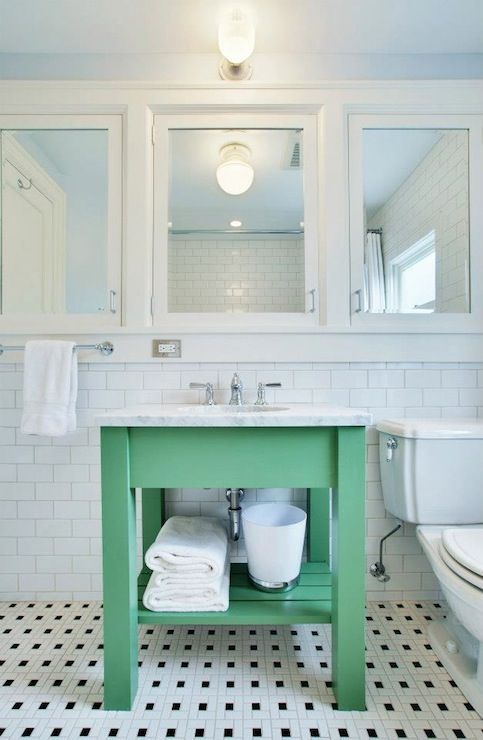 White and green bathroom with row of white framed medicine ...