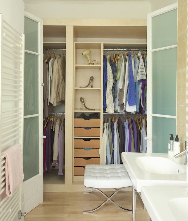 Closet Located Within Bathroom Features Frosted Glass Folding Doors Leading To Blonde Built In Cabinets