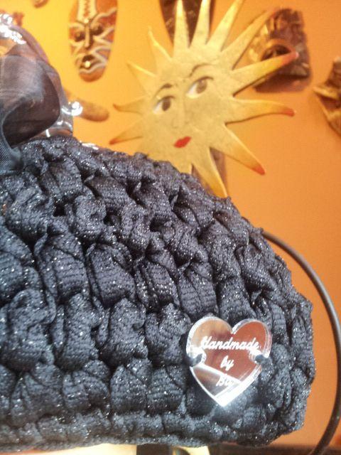 """Ultima nata per brillare nelle feste di Natale. In fettuccia di cotone nera e lurex, """"The star"""" il suo nome come la charm a forma di stella che lega un fiocco di tafta`, manico in stile retro` interno con stoffa giapponese rossa."""
