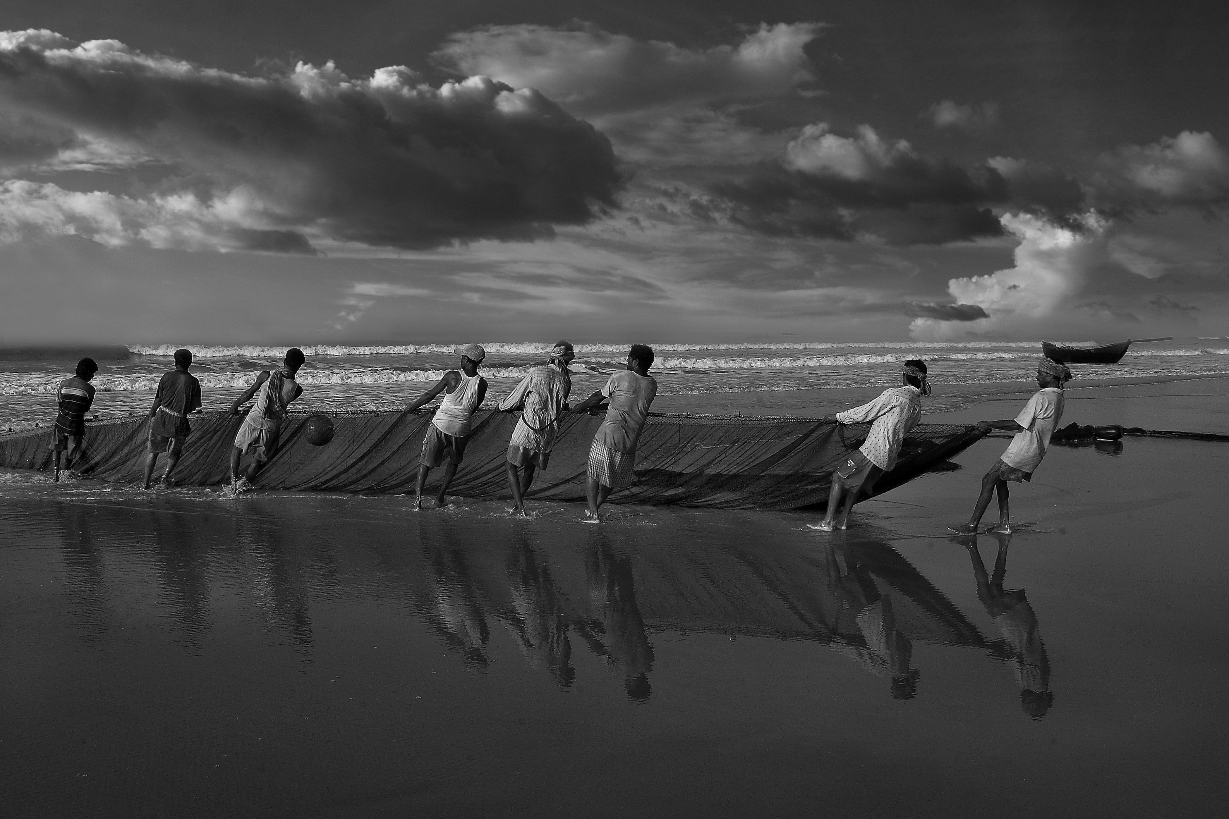 Black And White Photograph Of Fishermen Hauling Nets On Digha Beach Taken