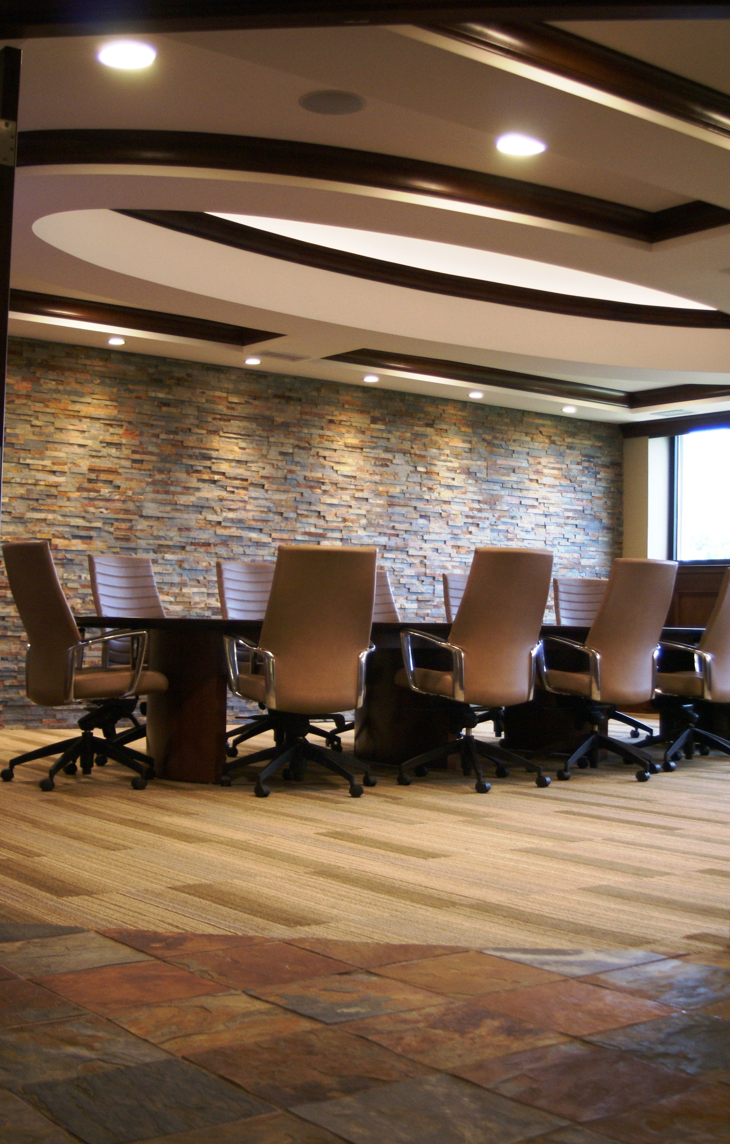A Conference Room With A Stone Wall To Accent The Decor Beautiful
