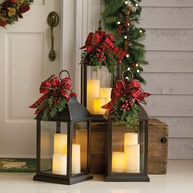 Lantern with removable holiday trim makes a bold statement on your porch or in your foyer Made of sturdy resin with glass panes it holds three batteryoperated LED candles...