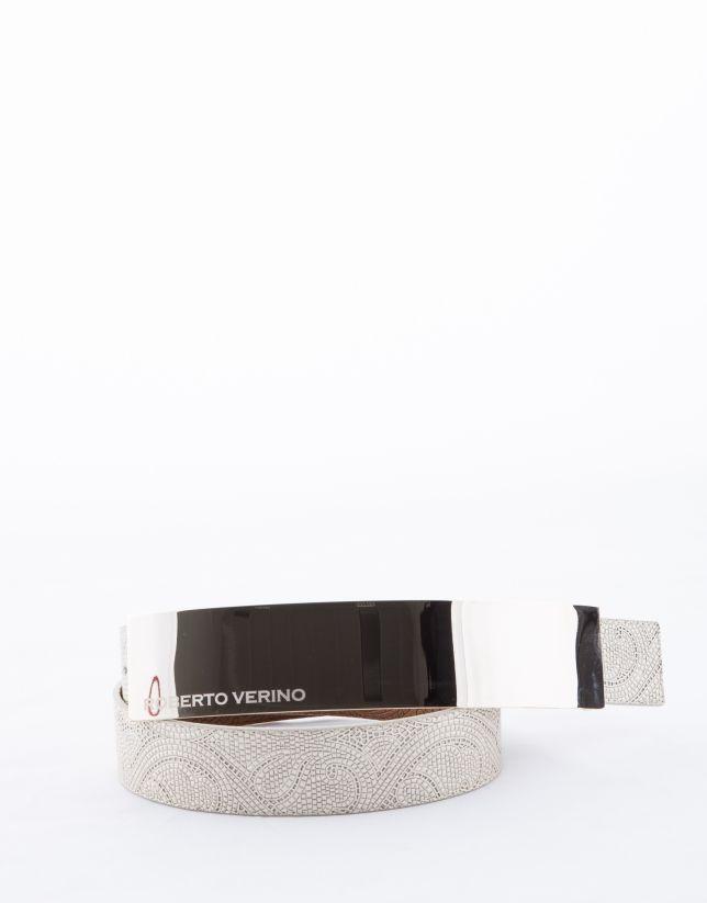 Cinturón en piel vacuno crudo perlado, estampado fantasía. Hebilla oro claro personalizada de 20 cm de largo. Ancho: 3.5cm