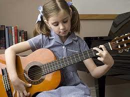 A guitarist in training strikes a G chord