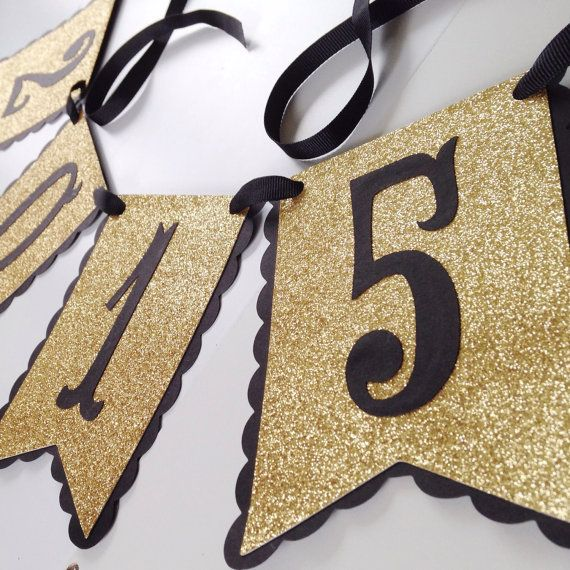 Heavy duty cardstock banner reads 2015 in black lettering on glittering gold and black pennants. Each pennant is approximately 6x3. Perfect for