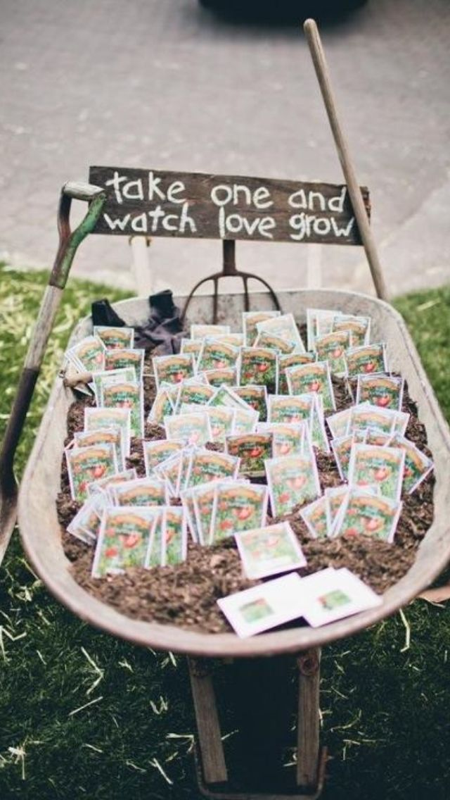Love this wheelbarrow with seed packets for weddings. Take one and watch love grow :)