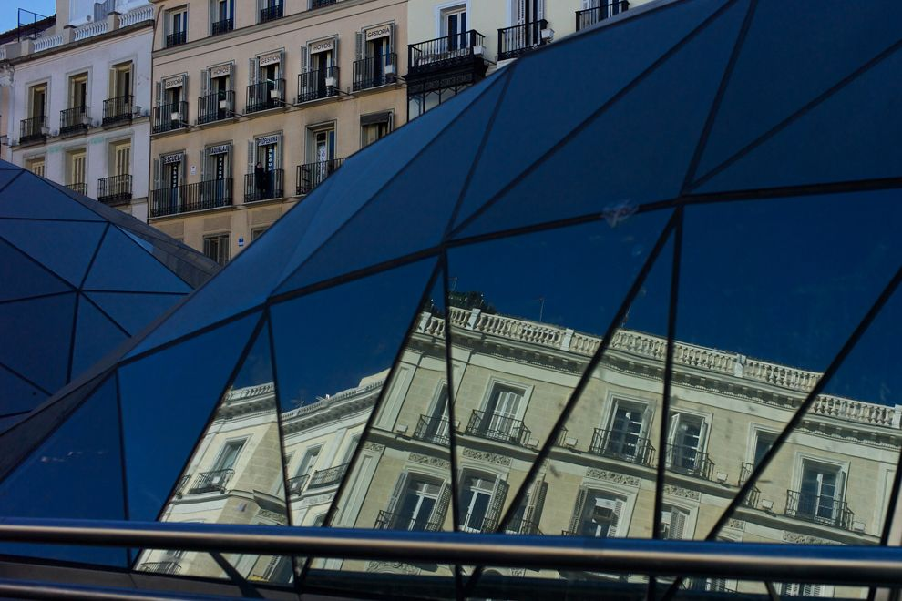 A building is reflected in a glass dome of an underground station in Puerta del Sol square in Madrid, Spain