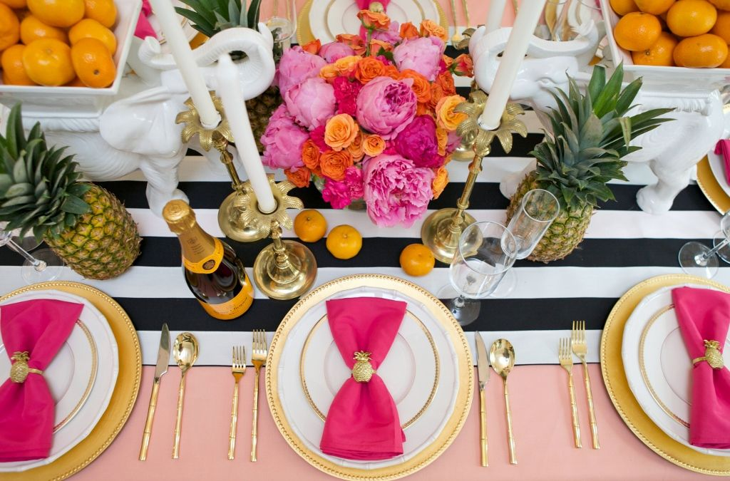 Fabulous tropical tablescape. Black and white stripes, gold rimmed dinnerware and gold bamboo handled flatware, cute pineapple napkin rings, palm tree candlesticks and hot pink and citrusy orange flowers.