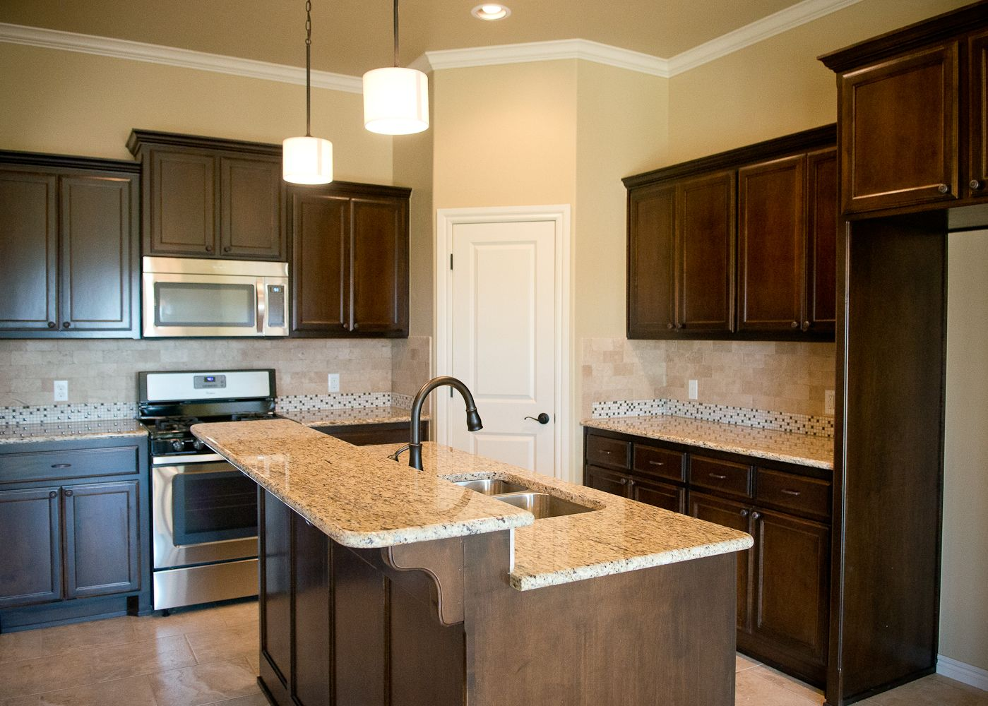 Beacon Homes Kitchen Warm Stained Cabinets Tumbled Travertine Backsplash Oil Rubbed Bronze