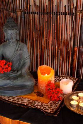 Buddha, flowers and candles set in a natural backdrop. Very zen ...