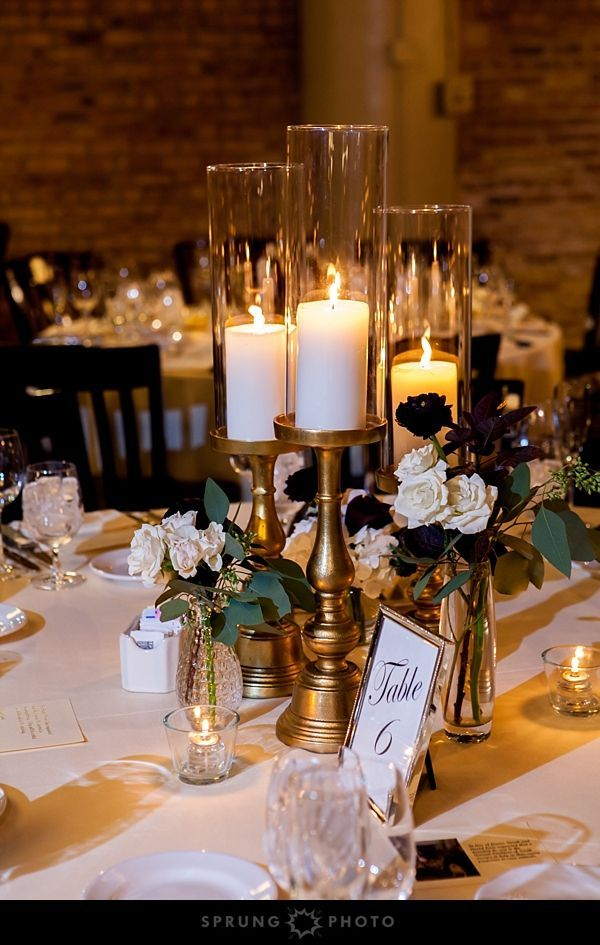 Tall Candles In Gold Candleholders And White And Maroon Flowers In