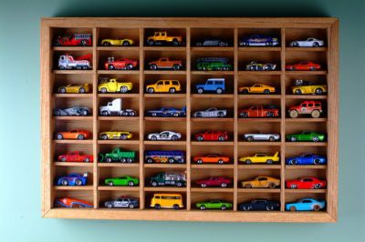 Holds 48 Matchbox cars.  Going to attempt to make it at home. Measures 16 x 24 x 2.5 deep.  Compartments measure 3.5 x 1.5 x 1.5 deep.  Has a sliding recessed plexiglass front panel.