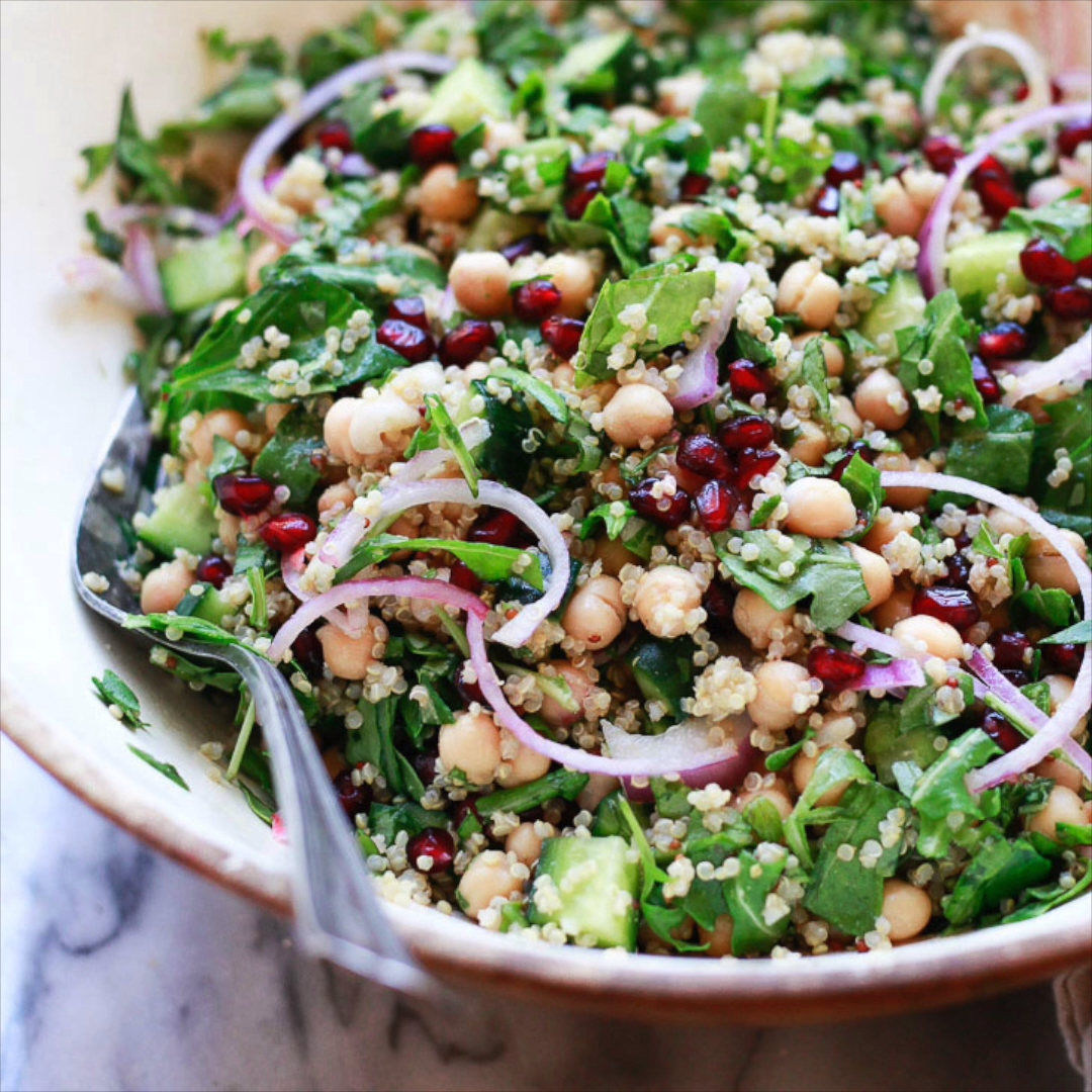 Chickpea and quinoa salad with spinach, pomegranate, red onion, cucumber and avocado. This savory c