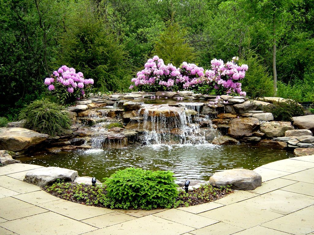 Traditional landscape yard with stacked stone waterfall for Pond water features