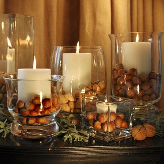 This photo is from Good Housekeeping as a Thanksgiving centerpiece. Assorted sizes and shapes of containers that are filled with mixed nuts and white candles. A bit of twig and greenery on the table also. So simple and looks so great….