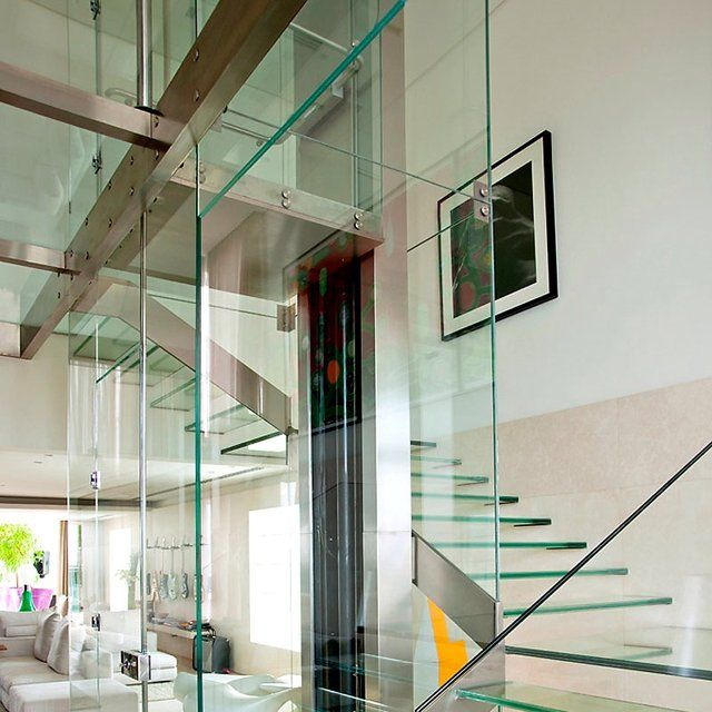 Glass stairs pivot around a steel and glass elevator shaft for Modern home elevators