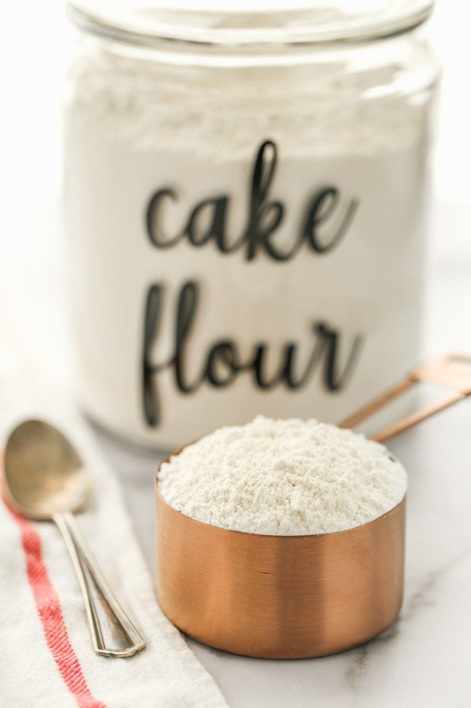 A copper measuring cup filled with cake flour and a ...