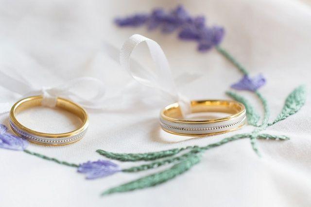 Zweifarbige Eheringe mit Perlierung, arrangiert auf einem mit #Lavendel bestickten Tuch. #Ringkissen #Trauringe #Hochzeit Foto: The Little Wedding Corner