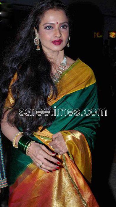 Bollywood actress Rekha in enticing green kancheepuram silk saree with contrast mustard wide borders.