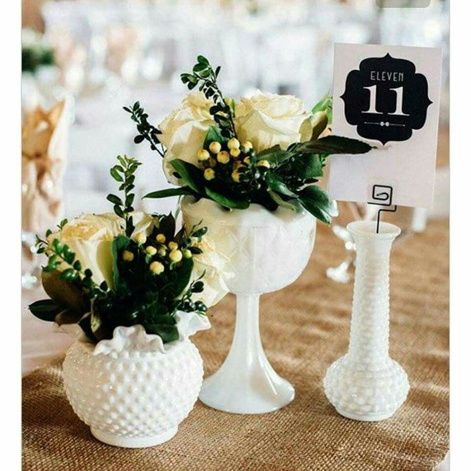 Small floral arrangements and table number holders displayed in white milk glass.